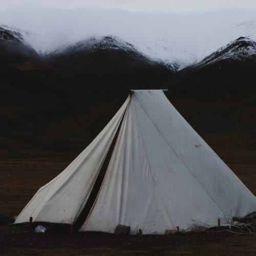 A white tent pitched near mountains.