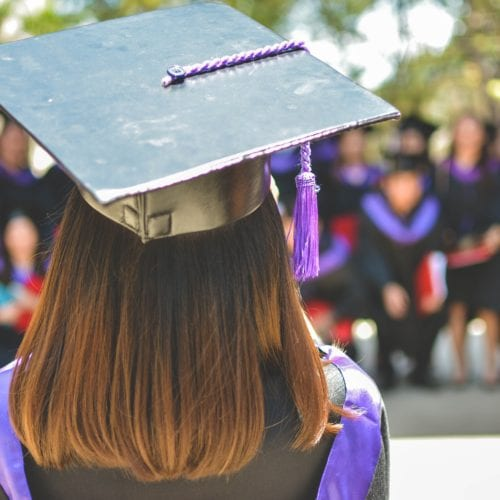 A young woman wearing a cap and gown.