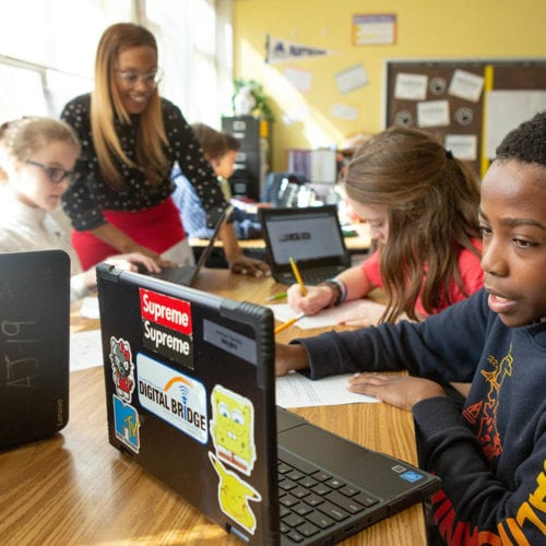Photo of middle school students working on their laptops.